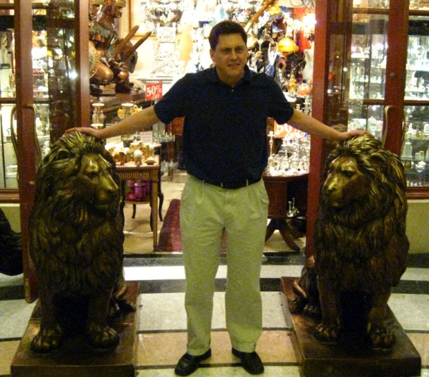 Brian poses with some lion statues.