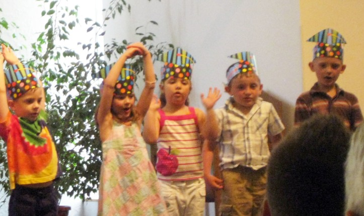 Emerson, middle, performs at her preschool graduation.