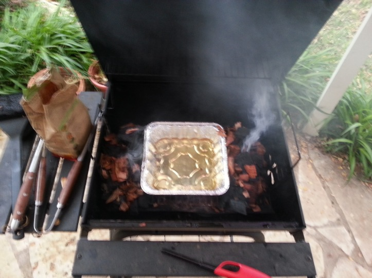 Prepping the grill. A drip pan full of Lone Star surrounded by two piles of a hardwood charcoal/mesquite wood chip mix.