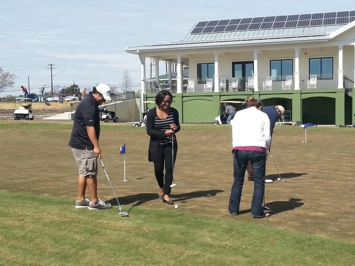Eddie, Shenea, and Allison practice their putting.