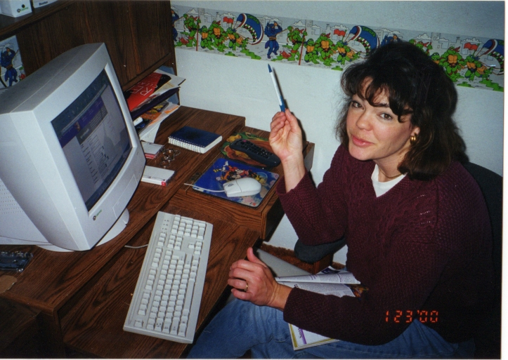 Mom pecking away at the computer with Ninja Turtle wallpaper.