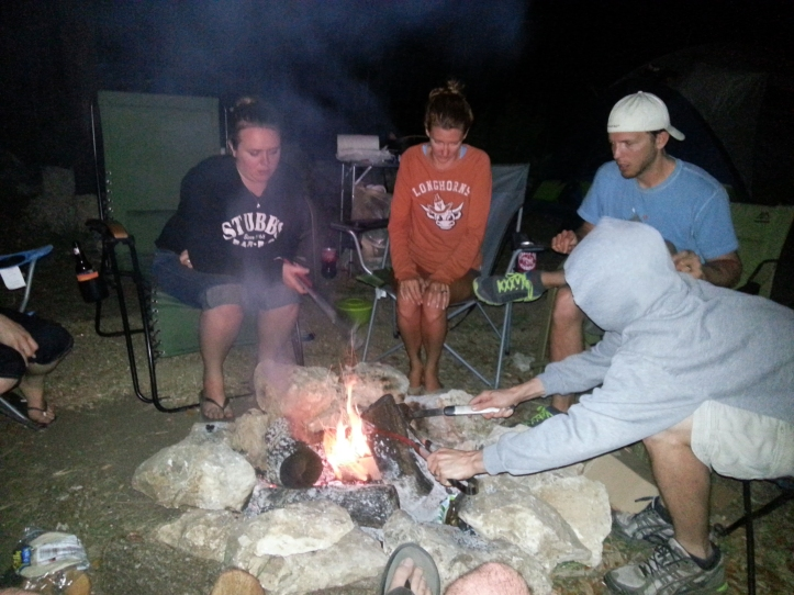 The gang keeps warm over a roaring campfire.