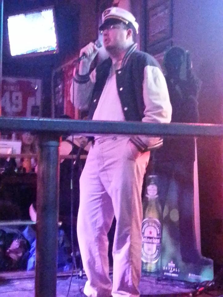 Karaoke teammate Geoff sings while wearing a sailor hat.