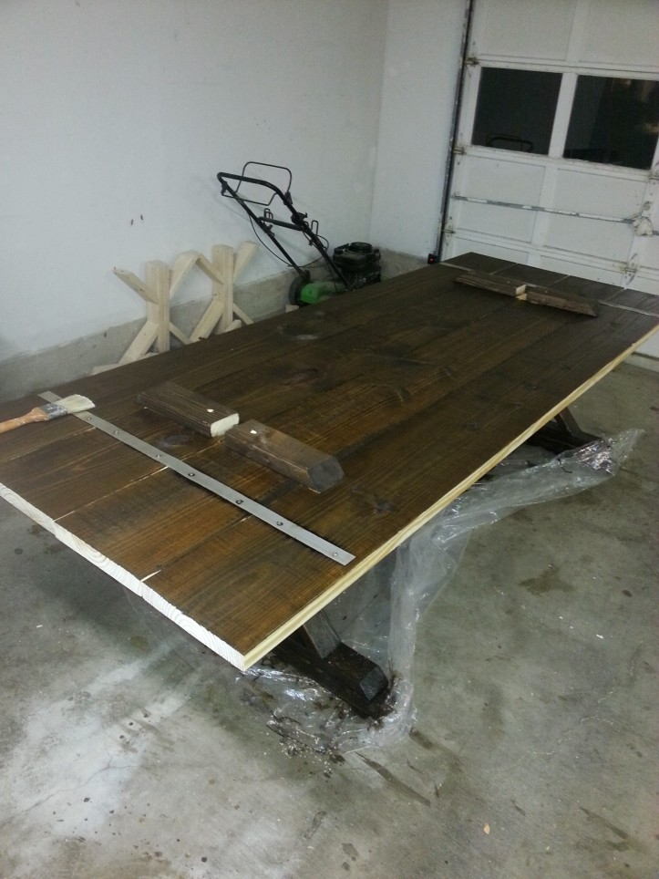 The bottom of the table with a coat of stain on it.