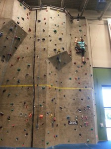 Elizabeth courageously reaches the top of an advanced rock wall.