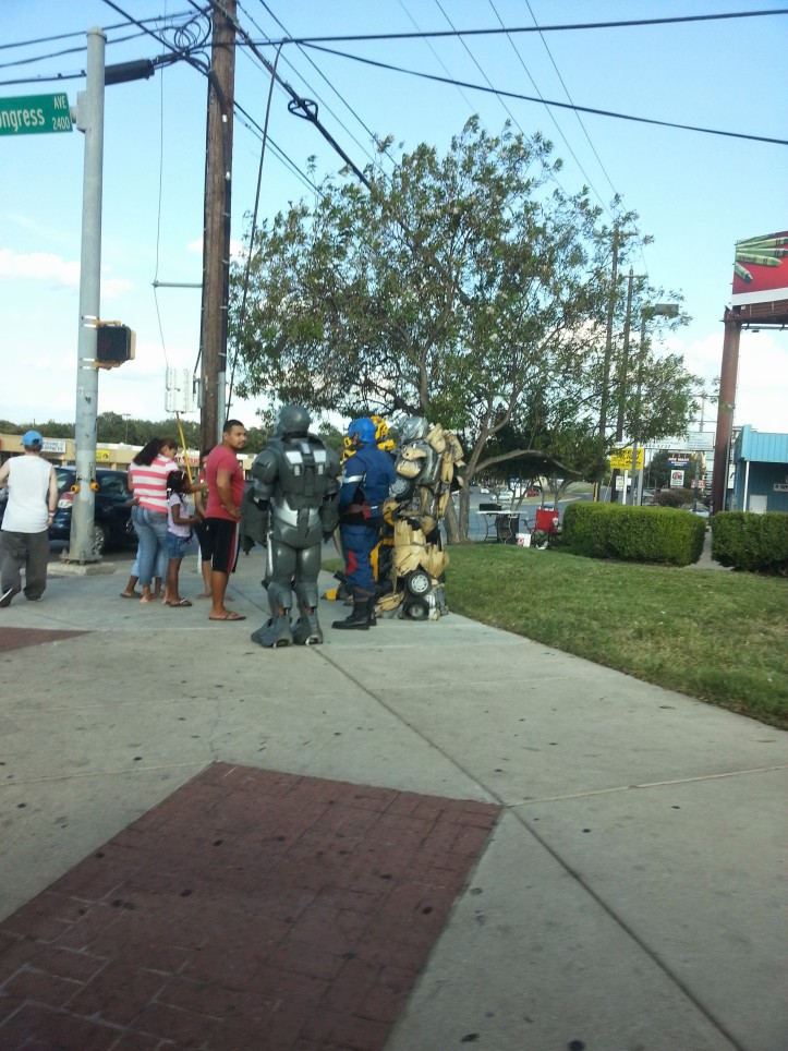 Some random robotic super heroes standing on a street corner for an apparent reason.