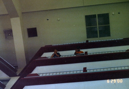 Unidentifiable people peering over a balcony at an unidentifiable hotel.