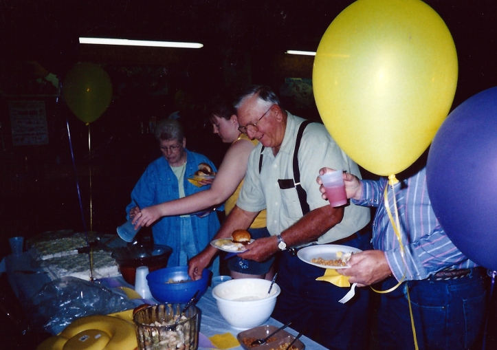 Some random unidentified members of the community eagerly scooping up food to fill their gullets at a celebration.