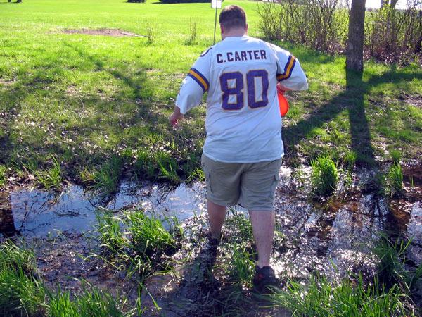 Jason wading through murky water while playing frisbee golf.