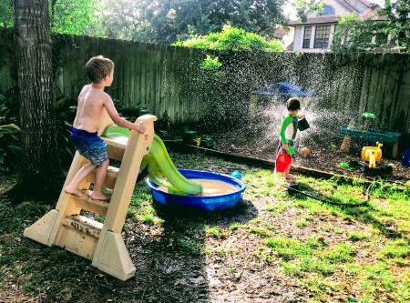 kids playing kiddie pool summer fun splashing sprinkler water